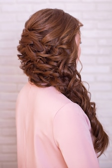 Female back with long, curly, brunette hairstyle