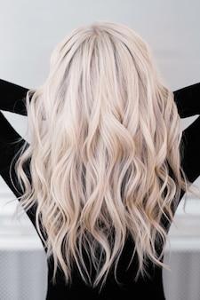 長い巻き毛の自然なブロンドの髪を持つ女性の背中