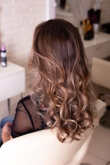 Женская спина с длинными, вьющимися, омбре, волосами брюнетки, в парикмахерской
