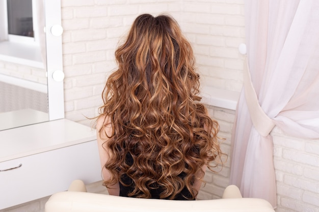 Female back with long, curly, ombre, brunette hair