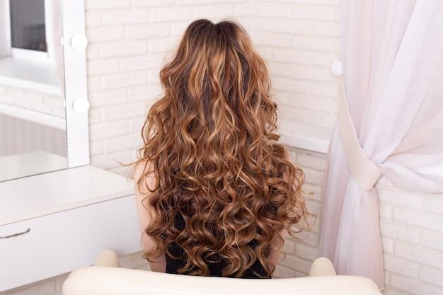 Женская спина с длинными вьющимися волосами цвета омбре, брюнетка