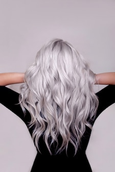 Female back with long curly silver blonde hair