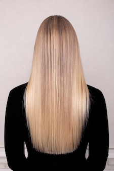 Female back with long straight blonde hair in hairdressing salon