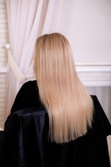 Female back with long, straight, blonde hair, in hairdressing salon