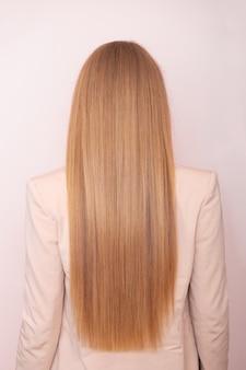 Женская спина с длинными прямыми светлыми волосами в парикмахерской