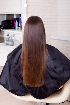 Female back with long straight brunette hair in hairdressing salon
