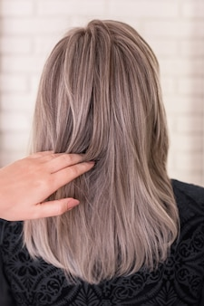 Female back with long, straight, grey, blonde hair