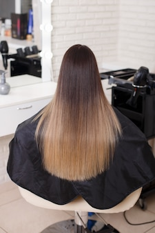 Female back with long straight ombre brunette hair in hairdressing salon