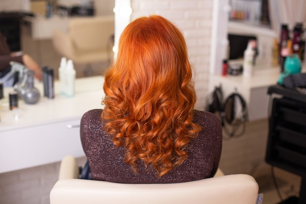 Female back with red hair on hairdressing salon