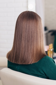Female back with short brunette hairstyle on hairdressing salon background