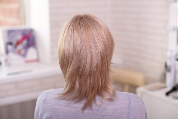 Female back with short thin blonde hair in hairdressing salon