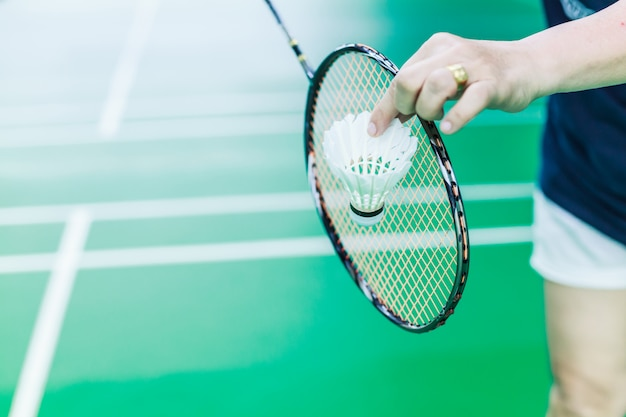 Female badminton single player hand hold white shuttle cock with racket