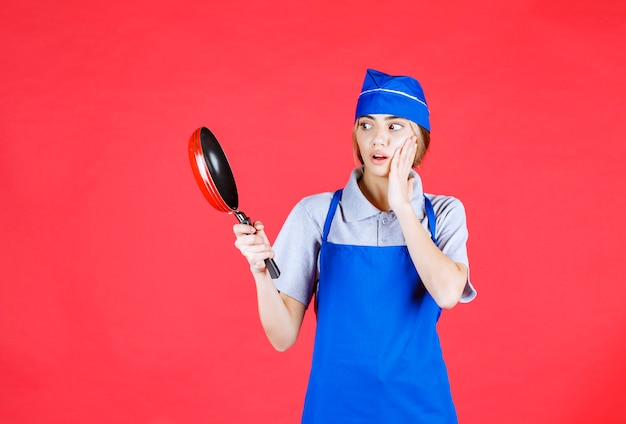 Female baker in blue apron holding a tefal frying pan and looks confused and thoughtful