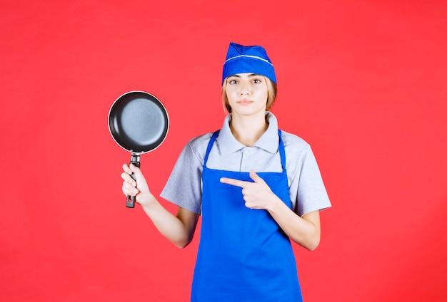 Female baker in blue apron holding a tefal frying pan