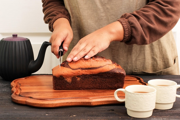 Female baker hold knife to cut loaf marble cake in the kitchen, about to serve with tea for afternoon teatime