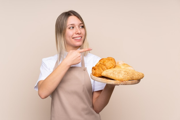 제품을 제시하기 위해 측면을 가리키는 여러 빵으로 테이블을 들고 여성 베이커