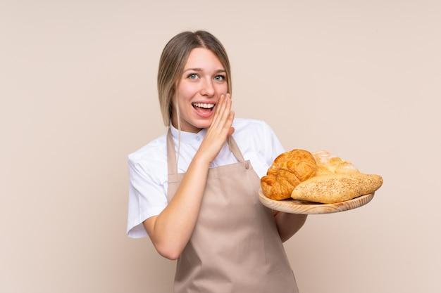 何かをささやくいくつかのパンのテーブルを保持している女性のパン屋