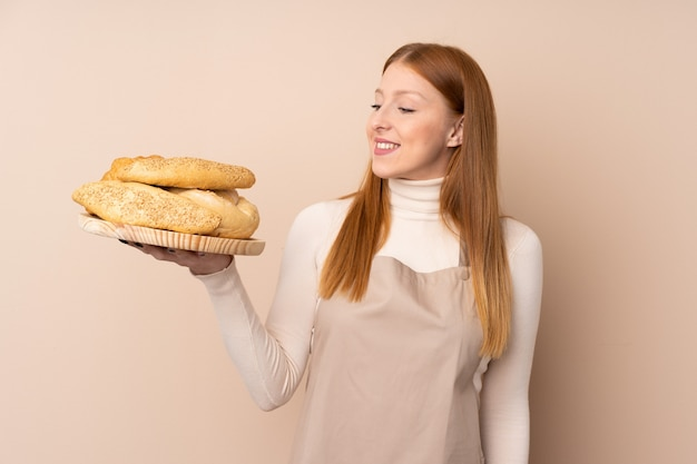 Female baker holding a table with several breads with happy expression