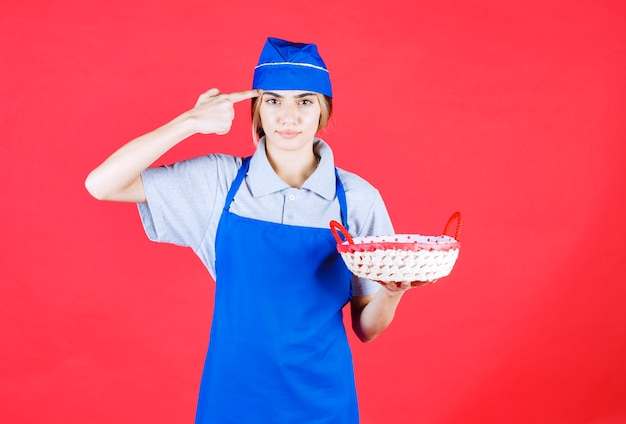 中に赤いタオルとパンのバスケットを保持し、混乱して思慮深く見える青いエプロンの女性のパン屋