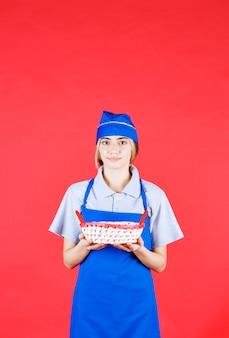 Женщина-пекарь в синем фартуке держит корзину для хлеба с красным полотенцем внутри