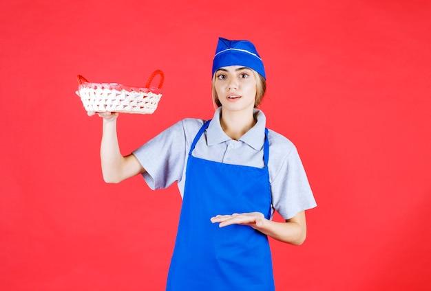 中に赤いタオルとパンのバスケットを保持している青いエプロンの女性のパン屋