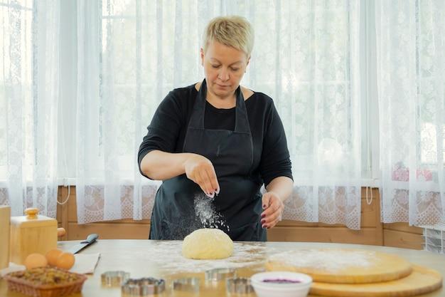女性のパン屋は台所で働いています