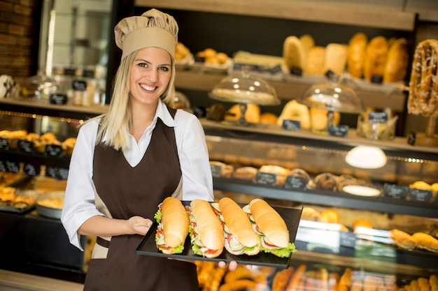 Female baker posing with various types of sandwiches in the baker shop