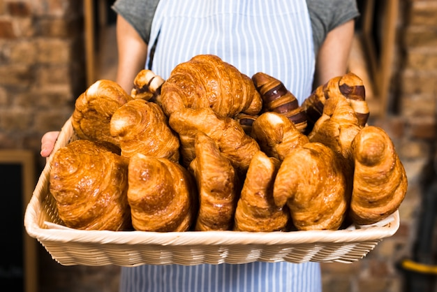 Female baker's hand holding basket of baked croissant