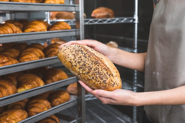 Female baker's hand holding fresh loaf of bread