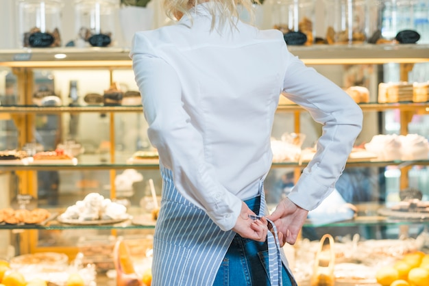 Female baker standing in front of pastry cabinet tying apron on her waist