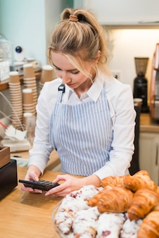 Female baker standing in her coffee shop using the calculator