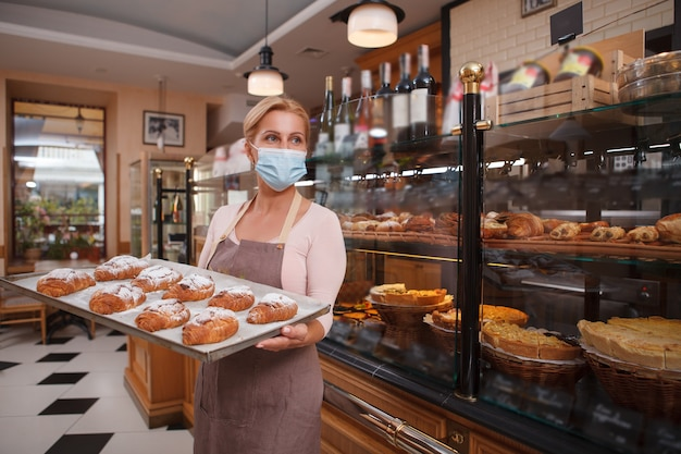 Female baker wearing medical face mask, selling croissants at her bakery store during covid-19 pandemic