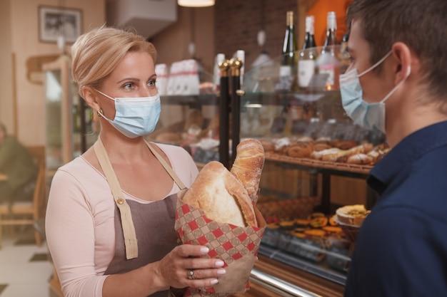 코로나 바이러스 전염병 동안 일하는 그녀의 남성 클라이언트 빵 덩어리를 전달하는 동안 의료 마스크를 착용 한 여성 베이커