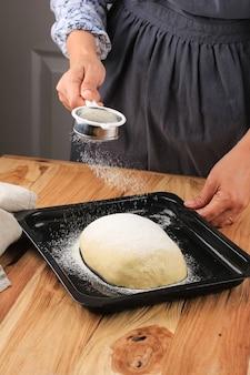 Женщины-пекари держат ситечко, покрывая сырое хлебное тесто с мукой, процесс выпечки приготовления молочного хлеба или мирукухасу, японского белого пушистого хлеба или пиццы