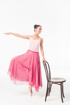 Female ballerina dancer standing on one leg holding chair
