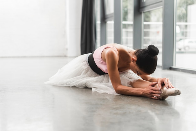 Female ballerina sitting on floor stretching