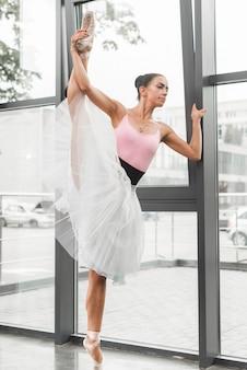 Female ballerina stretching her leg near the window