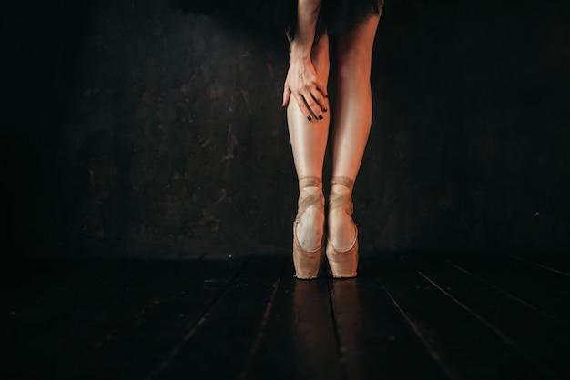 Ноги артистки балета в пуантах, черный деревянный пол. балерина в красном платье и черном танцует на сцене театра