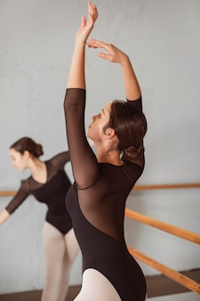 Female ballet dancers training together in leotards and pointe shoes