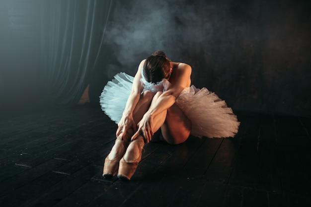 Артистка балета в белом платье сидит на полу, гибкость тела. тренировка балерины в танцевальном классе