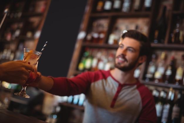 Женский барный тендер дает бокал коктейля клиенту