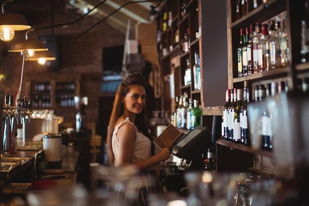 Female bar tender holding menu