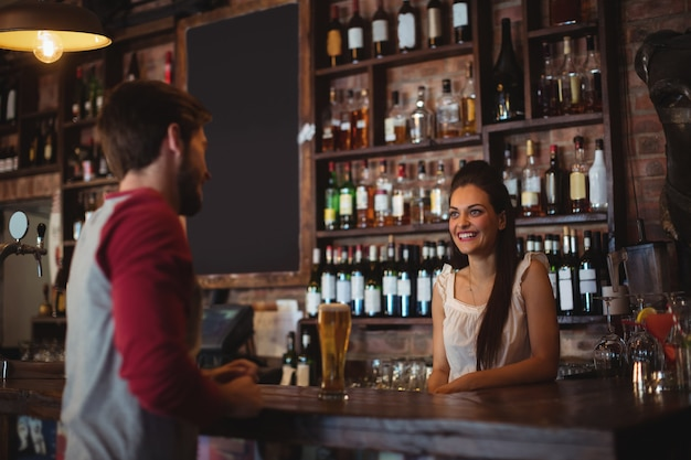 Женский барный тендер, взаимодействующий с клиентом