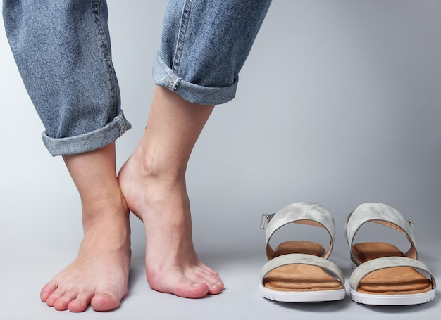 Female bare feet in jeans and sandals on white..