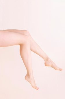 Female bare legs raise, on a beige wall. beauty salon, depilation, care, medicine, varicose veins, cosmetic surgery, spa and treatment concept.
