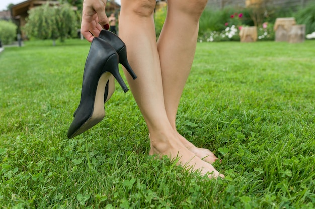 Female barefooted legs on green lawn