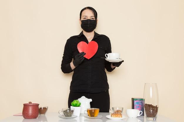 Barista femmina in pantaloni camicia nera con caffè marrone essiccato ingredienti tè attrezzature in maschera sterile nera sul muro bianco