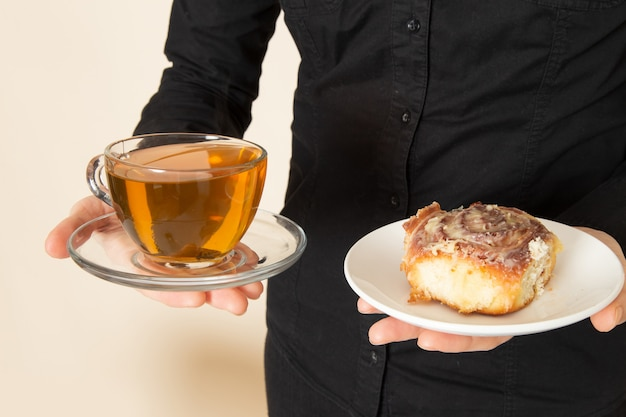 Female barista in black shirt trousers with coffee brown dried tea equipment ingredients on the white wall
