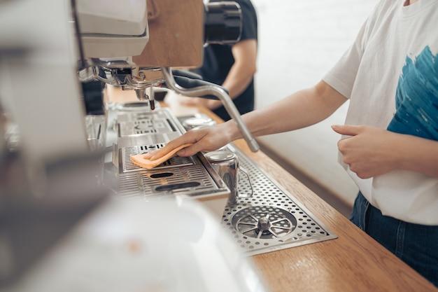 カフェテリアでコーヒーマシンを掃除する女性のバリスタ