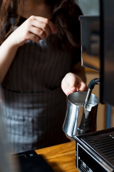 Female barista hand steaming milk for latte in stainless steel pitcher
